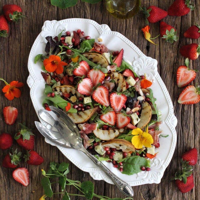 Salada de folhas com pera grelhada, presunto, queijo, bagos de romã, morangos e amêndoa laminada torrada